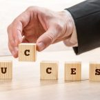 Close up Hand of a Businessman Arranging Small Wooden Blocks on the Table for Success Concept.